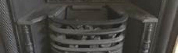 Travertine surround with cast iron hob black granite hearth