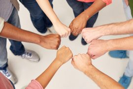 teamwork, friendship, international, gesture and people concept - group of hands making fist bump